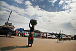 A woman waits to cross a busy street at a food market in Accra, Ghana.