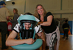 Torrington, CT 051719MK01  Logan Kovall gets a massage from Jennifer Romanchick, from Healing Root, during the Health and Wellness Festival at the Torringford School Friday evening.  Erica McMurdy, school physical education teacher and event coordinator, said that 50 vendors manned tables and stations to offer activities along with information on ways to improve their health and live a healthier lifestyle.  McMudry stated that she expected over five hundred participants to partake in the event and take home healthy swag to share with family members. Michael Kabelka / Republican-American