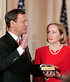 Washington, DC - September 29, 2005 -- John Glover Roberts, Jr. , left, is sworn-in as the 17th Chief Justice of the United States by Associate Justice John Paul Stevens in the East Room of the White House in Washington, D.C. on September 29, 2005.  His wife, Jane Sullivan Roberts, right, holds the bible..Credit: Ron Sachs / CNP