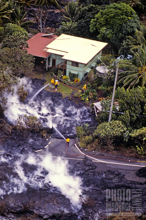 Kilauea volcano lava flow consuming homes in its path with people spraying water to slow the process