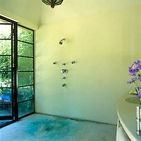 The large bathroom is designed as a wet room with a shower set in a corner next to the glass wall