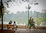 VIETNAM, Hanoi, two soldiers riding a bike in front of Hoan Kiem Lake, Two people sitting on a bench
