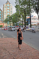 Pretty Vietnamese girl walking in the streets of Saigon or in Vietnamese Ho Chi Minh City where old and new architecture mix in harmony. The bustling Metropolis of South Vietnam.