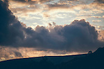 Dark clouds over a hilly landscape at sunset