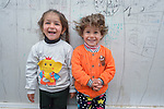 "Displaced children pose outside their familiy's ""caravan,"" a manufactured housing unit offered to some displaced families in the village of Bakhtme, Iraq. The community was flooded with displaced families when the Islamic State group took over nearby portions of the Nineveh Plains in 2014. The community includes a ""child-friendly space"" sponsored by the Christian Aid Program Nohadra - Iraq (CAPNI), offering displaced children and children from the host community an opportunity to play and learn."