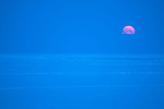 The moon sinks toward the horizon as the sun rises in the Bering Sea in springtime.