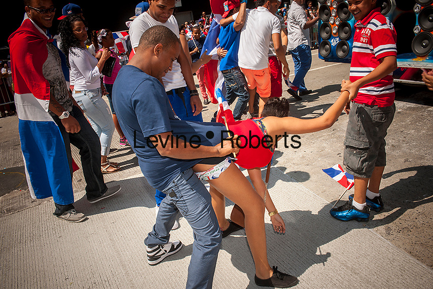 """Participants indulge in """"dirty dancing"""" during the Dominican Day Parade in New York on Sixth Avenue on Sunday, August 11, 2013.  Politicians, flags and cultural pride were on display at the annual event.  (© Richard B. Levine)"""