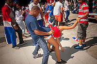 "Participants indulge in ""dirty dancing"" during the Dominican Day Parade in New York on Sixth Avenue on Sunday, August 11, 2013.  Politicians, flags and cultural pride were on display at the annual event.  (© Richard B. Levine)"