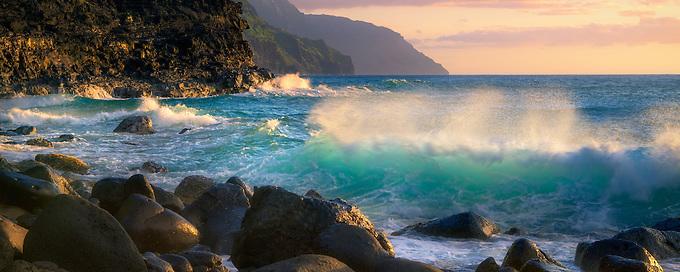 Soft sunset light reflectes off the ocean shore looking towards the Na Pali Coast, Hawai'i.