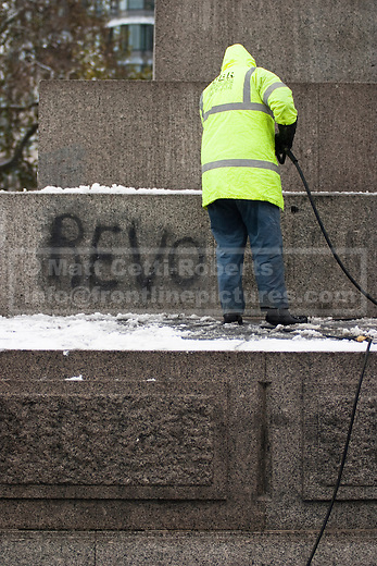 A worker uses a high pressure hose to remove the word 'REVOLUTION' from the base of Nelson's Column.  The third protest resulted in demonstrators being 'kettled' in an small area around the landmark. 02/12/10