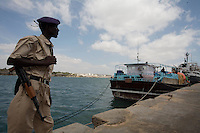 A Somali Transitional Federal Government police officer patrols the Mogadishu port, Somalia on Saturday Dec 30 2006.. Only a few days after the fall of the United Islamic Courts in Mogadishu, Ethiopian and Transitional Federal Government troops are patrolling the city and securing strategic locations..The people in Mogadishu appear confused and doubtful on t