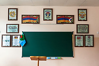 """Nagorno-Karabakh, also known as Artsakh, is a landlocked region in the South Caucasus. Stepanakert is the capital and the largest city of the Republic of Artsakh (better known as Nagorno-Karabakh). """" Hovhannes Tormanyan"""" Secondary School No 9. Classroom with green blackboard. Two flags Armenia (L) and Nagorno-Karabakh (R). On June 2, 1992, the self-proclaimed Republic of Artsakh adopted a flag derived from the flag of Armenia, with only a white pattern added. A white, five-toothed, stepped pattern was added to the flag, beginning at the two verges of the flag's right side and meeting at a point equal to one-third of the distance from that side. The white pattern symbolizes the current separation of Artsakh from Armenia proper and its aspiration for eventual union with """"the Motherland."""" This symbolizes the Armenian heritage, culture and population of the area, and represents Artsakh as a separated region of Armenia by the triangular shape and the zigzag cutting through the flag. The white pattern on the flag is also similar to the designs used on rugs, a symbol of national identity. The national flag of Armenia, the Armenian Tricolour, consists of three horizontal bands of equal width, red on the top, blue in the middle, and orange (also described as """"colour of apricot"""") on the bottom. The Armenian Supreme Soviet adopted the current flag on 24 August 1990. On 15 June 2006, the Law on the National Flag of Armenia, governing its usage, was passed by the National Assembly of Armenia. Nagorno-Karabakh is a disputed territory, internationally recognized as part of Azerbaijan, but most of the region is governed by the Republic of Artsakh (formerly named Nagorno-Karabakh Republic), a de facto independent state with Armenian ethnic population.  Since 1994, regular peace talks between Armenia and Azerbaijan mediated by the OSCE Minsk Group have failed to result in a peace treaty. Hovhannes Tumanyan (1869 -1923) was an Armenian poet, writer, translator, literary and public act"""