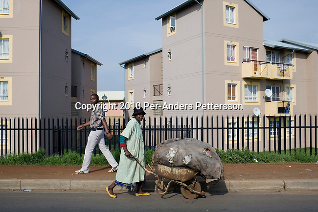 SOWETO, SOUTH AFRICA - JANUARY 15: A woman pushes a wheelbarrow with trash in front of a newly constructed security complex on January 15, 2010, in the Kliptown section of Soweto, South Africa. Soweto is the largest township in South Africa, located about 10 kilometers southwest of downtown Johannesburg. The population is estimated to be around 2-3 million. A growing black middle class can be seen in the township and many shopping malls and has been built the last few years. (Photo by Per-Anders Pettersson/Getty Images)