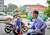 VIETNAM, Ho Chi Minh, Saigon, mother holding sleeping kid, scooters street scene
