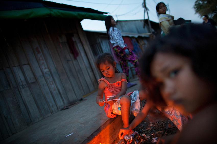 Children gather around a make-shift fire along the railway tracks that skirt the edge of Boeung Kak lake in Phnom Penh, Feb 4, 2011.