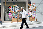 Yoshitomo Sasaki carries a wooden frame onto which have been hung several dozen Edo furin, or glass wind chimes, which he sells on the streets of chic Ginza district in Tokyo, Japan. The chimes, which date back more than 200 years in Japan, were traditionally carried around town dangling from  bamboo poles by sellers. Sasaki is one of a few people who continue this trend.