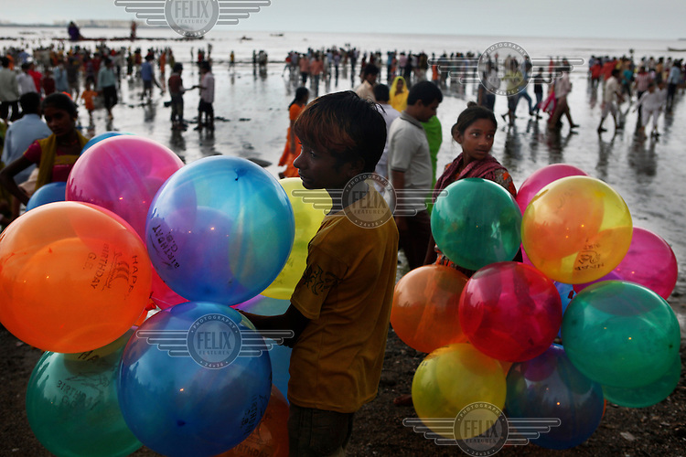 A boy selling balloons on Chowpatty Beach during the culmination of Ganesh Chaturthi. This is Mumbai's biggest and most explosive celebration. Held in honor of the much-loved elephant-headed god (here called Ganpati), the 10 day festival culminates on the last day, when a jubilant procession is held and thousands of huge Ganpati idols are immersed in the sea..