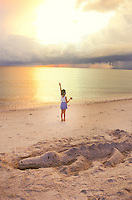 Salute to the sky, young girl child on beach seashore at dawn, raising her arm to greet the daybreak, with alligator sand sculpture, horizon of ocean water, sky, clouds