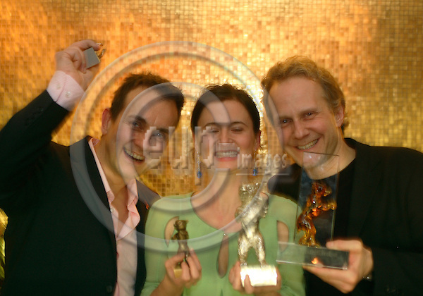 """BERLIN - GERMANY 18. FEBRUARY 2006 -- Berlin Filmfestival  -  Berlinale 2006   - At a party in Berlins Hotel Mandala  Danish Director Pernille Fischer Christensen, Producer Lars Rahbeck (L) and Childrens Film Director Niels Arden Oplev proudly display the evenings harvest of awards.  -- PHOTO: UFFE NOEJGAARD / EUP-IMAGES..This image is delivered according to terms set out in """"Terms - Prices & Terms"""". (Please see www.eup-images.com for more details)."""