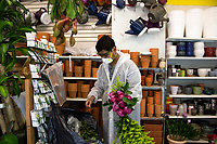 NEW YORK, NY - MAY 10: A man with a face mask and body protection arranges a bouquet of flowers at the Garden Center in Jackson Heights on Mother's Day on May 10, 2020 in Queens, New York. COVID-19 has spread to most countries in the world, claiming more than 283,000 lives and more than 4.1 million people infected, Queens has been one of the places most affected by the Coronavirus. (Photo by Pablo Monsalve / VIEWpress via Getty Images)