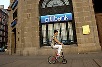 A woman rides a bicycle past a Citibank branch in Shanghai Bund. .