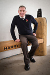 © Joel Goodman - 07973 332324 . 2 November 2013 . Chorlton Precinct (aka The Square ) Manchester , UK . NATHAN BIRKS , friend of Harry's , sits on the bench . A bench in memory of photographer Harry Goodwin is unveiled at Chorlton Precinct . The locally created carved wood design features two cameras , one a historic twin-lens reflex design and the other a modern 35mm design . Photo credit : Joel Goodman