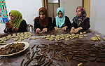 Palestinian youths prepare traditional cookies ahead of the Eid al-Fitr festivities, celebrating the end of the holy Muslim fasting month of Ramadan, at al-Maghazi camp in the center of Gaza Strip on May 29, 2019. Photo by Ashraf Amra