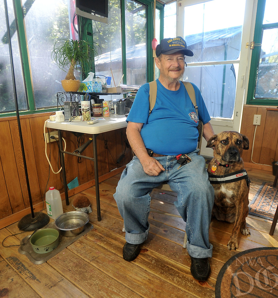 NWA Democrat-Gazette/MICHAEL WOODS &bull; @NWAMICHAELW<br /> Richard Ellett, a veteran with PTSD, sits in his front room Saturday September 12, 2015 with Tiger, his service dog he received in November.  The service dog was given to Ellett by Soldier ON,  a new non-profit that places puppies with puppy-raisers for one year to be trained as service dogs, to then be given to veterans with PTSD.