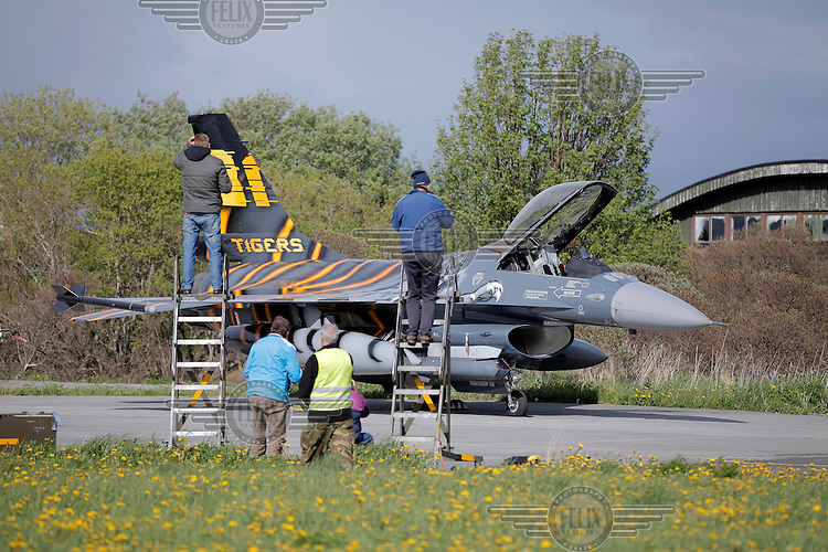 Plane spotters given access to a parking area photographs a Belgian F-16. Nato Tiger Meet is an annual gathering of squadrons using the tiger as their mascot. While originally mostly a social event it is now a full military exercise. Tiger Meet 2012 was held at the Norwegian air base Ørlandet.