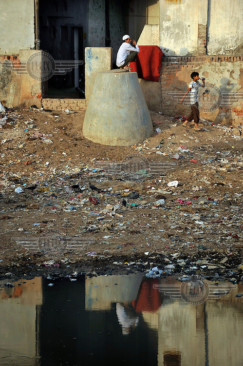 A man sits on a turret in a slum in the area of Nizamuddin East.