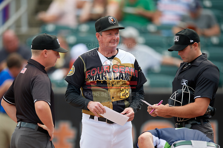 Aberdeen IronBirds manager Kevin Bradshaw (25) during the lineup exchange with umpires Paul Roemer (right) and Joe Belangia (left) before a NY-Penn League game against the Vermont Lake Monsters on August 18, 2019 at Leidos Field at Ripken Stadium in Aberdeen, Maryland.  Vermont defeated Aberdeen 6-5.  (Mike Janes/Four Seam Images)
