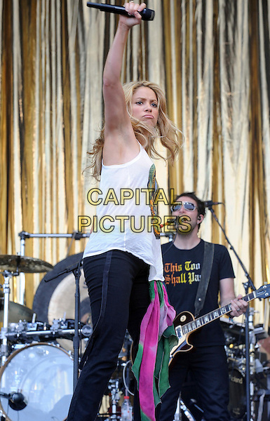 SHAKIRA .Perfoming live during Glastonbury Festival 2010, Worthy Farm, Glastonbury, England, UK, .June 26th 2010..Glasto music concert on stage gig .half length white vest top sleeveless  skull print Alexander McQueen motif microphone bracelets  scarf around waist green pink scarves  microphone arm raised up funny side .CAP/WIZ.© Wizard/Capital Pictures.