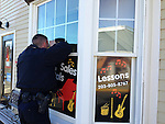 SOUTHBURY, CT - 25 Dec 2013 - 122513RH02 - Southbury Police Officer Brian McKirryher peers through a window of Southbury Music Studio in Southbury in response to an alarm triggered by a motion detector. Rick Harrison Republican-American