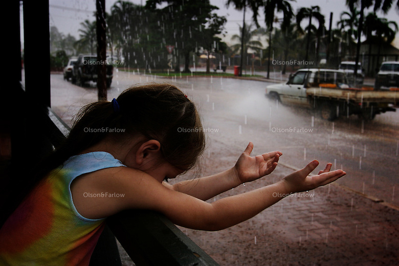 After a long hot build up, rain finally comes to Broome. This is taken in the historic Chinatown district as a family out shopping got caught in the storm.  <br /> <br /> Broome has 15,000 regular residents, but swells to 100,000 in tourist season..April 2000 Eye of cyclone went 40km south of Broome.80 mile beach is 50km south of Broome and gets horrendous weather... cyclones are always slamming this spot... not very inhabited though... just small communities.