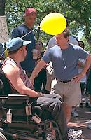 Senator Paul Wellstone talking with man in wheelchair age 35 at AIDS Walk ceremony.  St Paul  Minnesota USA