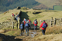 Walkers crossing a farm gate, Mellor Knoll, Forest of Bowland, Lancashire.