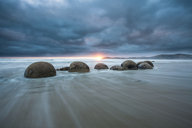 Cloudy sunrise over Moeraki Boulders, Coastal Otago, South Island, New Zealand - stock photo, canvas, fine art print