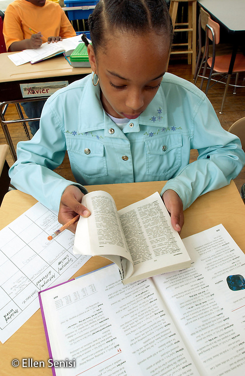 MR / Schenectady, NY / .Yates Arts in Education Magnet School / urban public elementary school / Grade 5.Girl (11, African-American) uses glossary in textbook and thesaurus to do language arts worksheet as part of independent work assignment.  Independent work is usually preparation or follow-up for reading or math class lessons done at a different time the same day.  .MR: AD-g5a Bla6..© Ellen B. Senisi