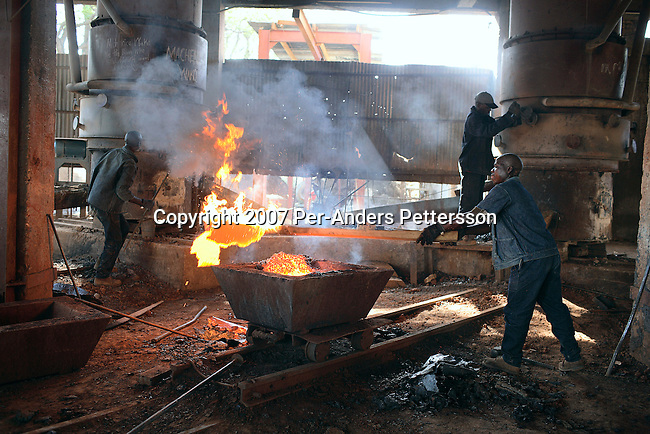 NDOLA, ZAMBIA MARCH 24: Unidentified Zambian workers toil in a copper smelter on March 24, 2007 in Ndola, Zambia. Eastern Union Limited is a China based company who buys Copper from Congo DRC, and brings it to Ndola to their Copper smelter. The smelter was shipped from China and operates 24 hours a day in an Industrial area in Ndola. The copper is eventually trucked to Dar es Salaam in Tanzania and on ships to China. The Chinese industry's thirst for raw materials has seen metals prices increase a lot the last years. Tens of thousands of Chinese has come to Africa the last years to work in infrastructure projects and businesses. Chinese companies are often the lowest bidders for contracts, pricing out the more expensive European companies. The Chinese people often live where they work and rarely interact with the local population. Most Chinese don't speak English and they are mostly staying in the compounds cooking their Chinese food, and watching Chinese Television and DVDs. (Photo by Per-Anders Pettersson)...