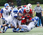 UK players tackle UL junior runningback Senorise Perry during the first half of the UK vs. UL football game at Papa John's Cardinal Stadium in Louisville, Ky., on Sunday, September 2, 2012. Photo by Tessa Lighty | Staff
