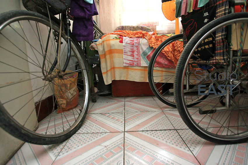 Li Yan's wheel-chair's wheels next to her father's bicycle's, in her home in Yinchuan, Ningxia Province, China, on May 7, 2007. 28-year-old Li Yan suffers from motor neuron disease also known as amyotrophic lateral sclerosis (or ALS), the same illness that has thereotical physicist Stephen Hawking. Li Yan asked China's National People's Congress (NPC) to consider a draft on euthanasia. Photo by Lucas Schifres/Pictobank