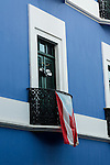 A Puerto Rican flag flies from the balcony of a olorfully painted house in the historic colonial city of Old San Juan, Puerto Rico.