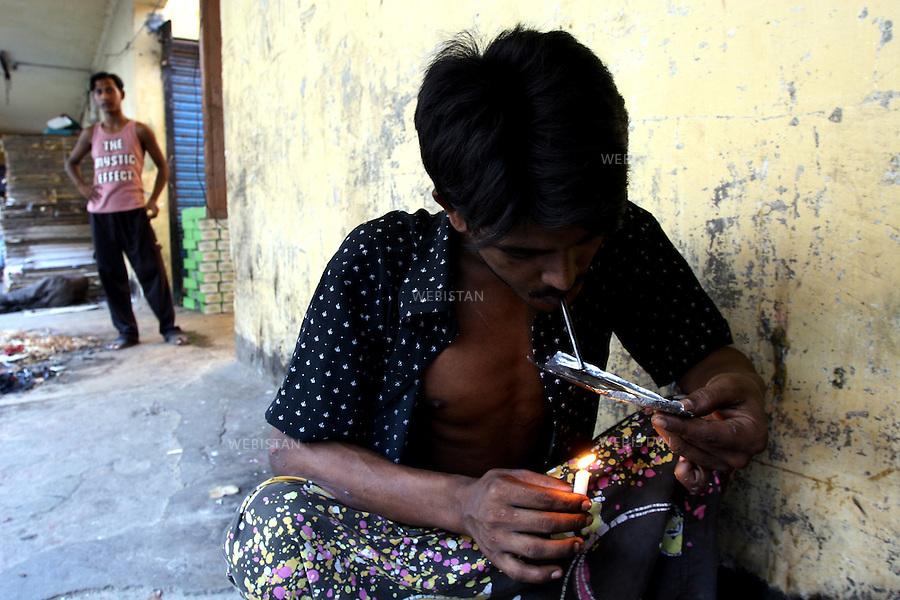2005. Bangaldesh, Dhaka. A user smokes a joint of heroin. ..2005. Bangaldesh, Dhaka. Un consommateur fume un joint d'héroïne...
