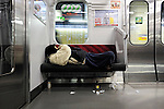 "A man sleeps as his discarded litter blows around under the seat on a train in Tokyo, Japan. The Japanese are well known for their civility and politeness,  but a recent governmental campaign to clamp down on lewd behavior that may inconvenience others -- including talking on cell phones and applying makeup while commuting on a train -- was fueled by a decline in everyday etiquette and manners. The series of posters has a headline that reads ""Please do it at home."""