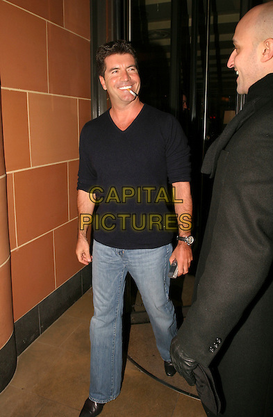 SIMON COWELL.Leaving Capriani Restaurant, London, UK..January 26th, 2006.Ref: AH.full length jeans denim smoking cigarette black top.www.capitalpictures.com.sales@capitalpictures.com.©Capital Pictures
