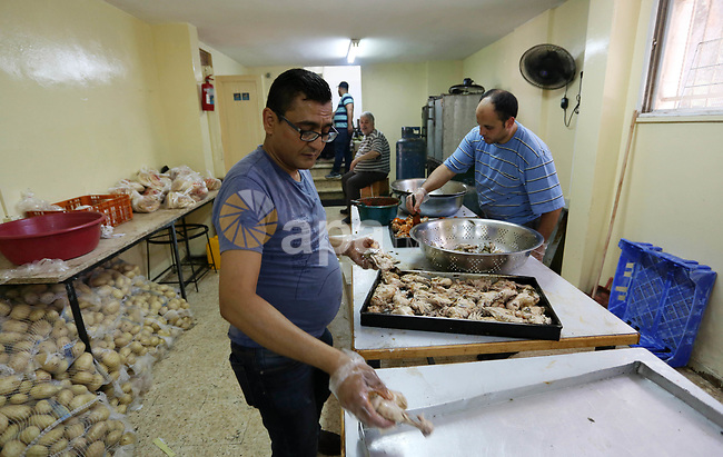 """Palestinian volunteers prepare rice and meats for distribution to the poor inside """"Nablus Takiya"""" which was founded in 2012 AD, and provides food for over than 1600 families daily during the holy Muslim month of Ramadan in the West Bank city of Nablus on May 21, 2018. Ramadan is sacred to Muslims because it is during that month that tradition says the Koran was revealed to the Prophet Mohammed. The fast is one of the five main religious obligations under Islam. Muslims around the world will mark the month, during which believers abstain from eating, drinking, smoking and having sex from dawn until sunset. Photo by Shadi Jarar'ah"""