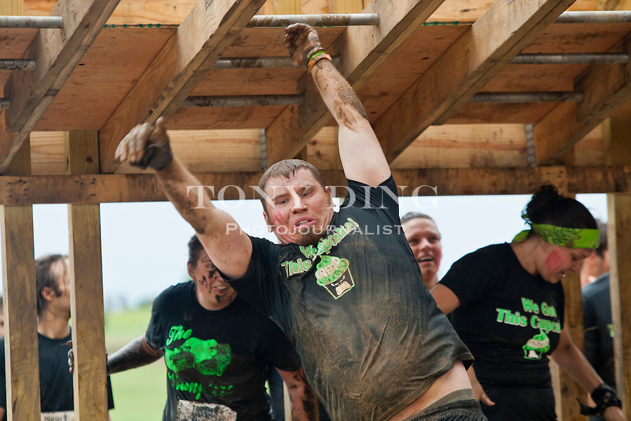 """16 April 2010: A competitor climbs through the """"Funky Monkey"""", one of twenty obstacles in the Tough Mudder adventure endurance race at Michigan International Speedway in Brooklyn, Michigan."""