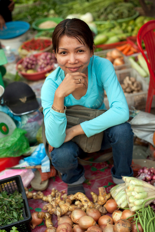 Portrait of a young woman vegetable vendor at a marketplace in Phnom Penh, Cambodia. <br /> <br /> Photos &copy; Dennis Drenner 2013.