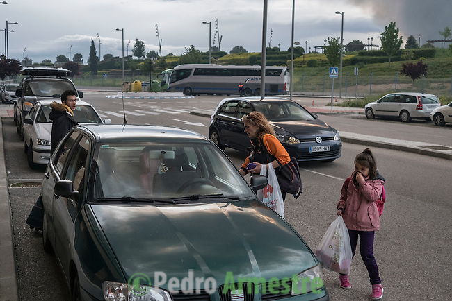A family evacuate a residential area in Sesena affected by the toxic fumes produced by tyres burning in an uncontrolled dump near the town of Sesena, after a fire broke out early on May 13, 2016. A huge tyre dump near Madrid was ablaze today, releasing a black cloud of toxic fumes and forcing the evacuation of nearby residents after what officials suspect was an arson attack.  © Pedro ARMESTRE