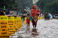 A Bangladeshi woman walks on a waterlogged street with her children after heavy rainfall in Dhaka, Bangladesh.